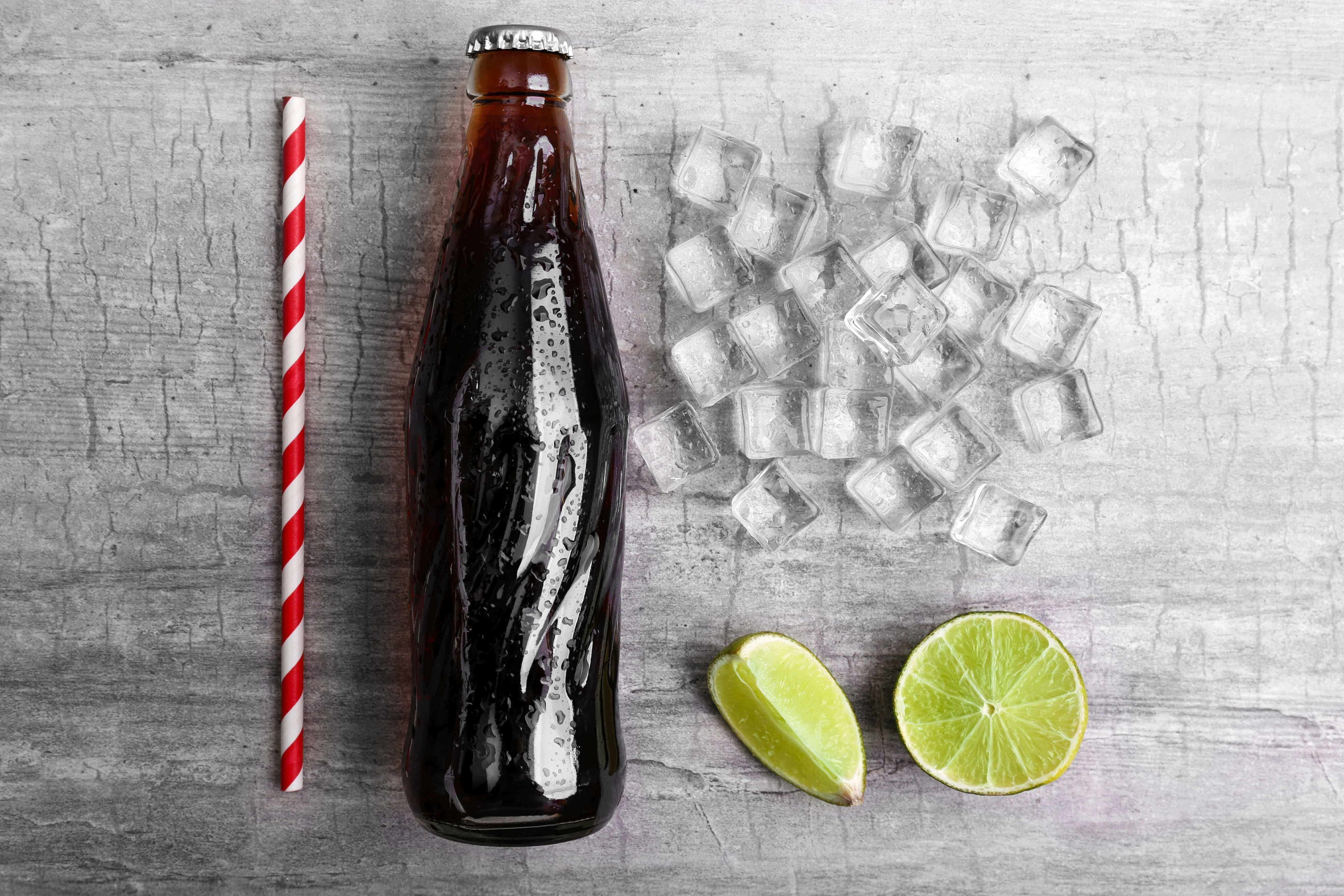 Plain cola bottle, ice, lime and straw