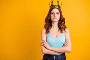 Confident woman wears crown against orange background