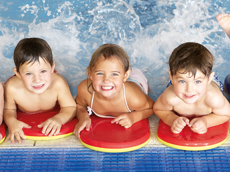 3 Happy Children Learning How To Swim