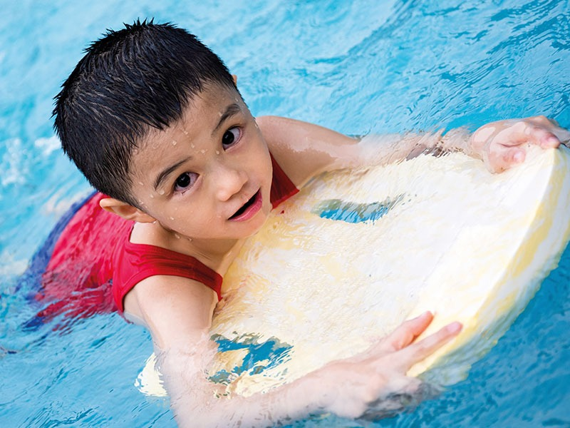 Young Child Learning How To Swim
