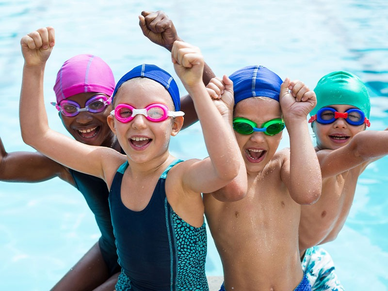 Group Of Happy Kids In Swimming Pool