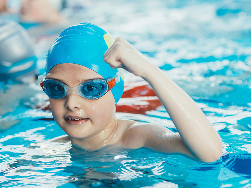 Young Pool In Swimming Hat And Googles In Pool