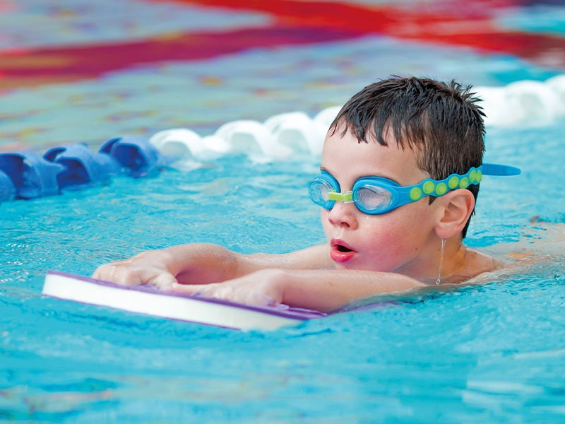 Young Boy Swimming In A Swimming Pool With A Float