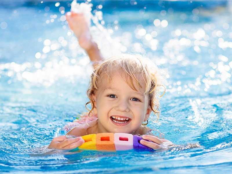 Happy Young Child In Swimming Pool Using Multi Colour Float