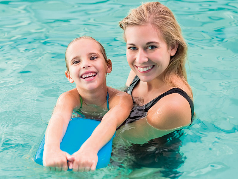 Happy Mother Teaching Her Daughter To Swim